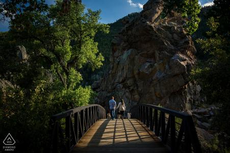 Fotografía previa a la boda de una pareja caminando sobre un puente de madera en el bosque.