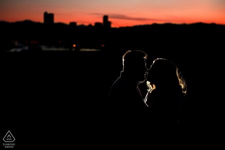 Photographe de fiançailles du Colorado travaillant une session de portrait de nuit avec une seule lumière et les toits de la ville