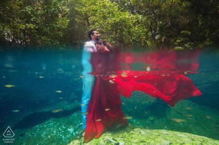 Photo d'engagement de Mumbai. À moitié sous l'eau avec sa robe rouge et son fiancé.