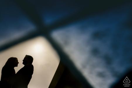 Silhouette portrait d'un couple abattu à travers une vitre brisée. Photographe de fiançailles Derbyshire