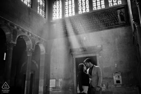 Fotógrafo italiano de compromiso. La luz del sol se filtra a través de las ventanas altas durante este retrato de interior en blanco y negro.