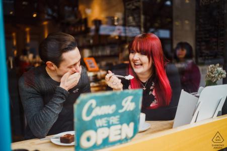 Fotografo di fidanzamento nel Regno Unito. La coppia della caffetteria condivide un morso.