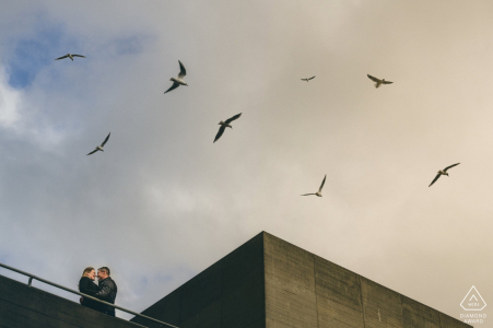 South Bank engagement photo shoot of a couple while birds fly above their heads