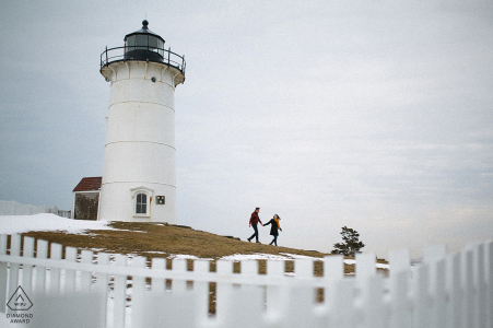 Boston Engagement Photograph at a New England lighthouse. White picket fences lead the way for this couple as they run hand-in-hand.