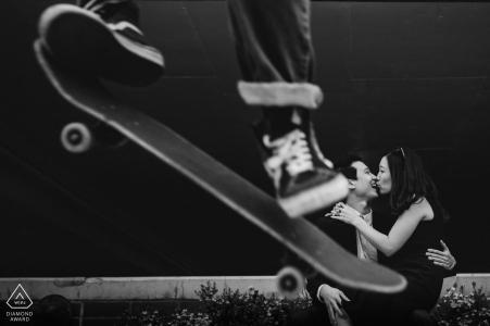 在一对亲吻的夫妇的订婚画象的前景的DC都市溜冰板者