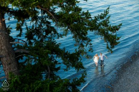 Kelowna couple walking in the water below a huge tree in British Columbia during their pre-wedding engagement shoot