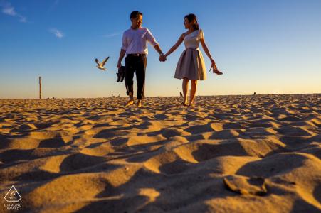 Südkalifornische Verlobungsfotos am Strand - Porträt eines jungen Paares, das Hand in Hand im Sand geht und seine Schuhe trägt, während eine Möwe dahinterfliegt
