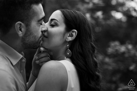 Lazio Black and white pre-wedding photography | a tightly cropped shot of a newly engaged couple kissing with their eyes closed