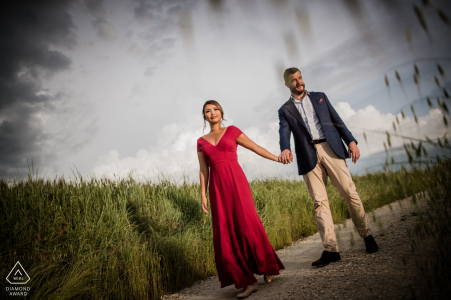 Her red dress and the slightly tilted frame provide excitement and drama in this Tuscany engagement portrait