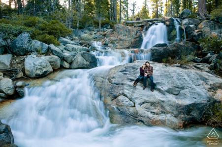 Couple du lac Tahoe est assis sur un rocher à côté d'une cascade avec un long volet lent
