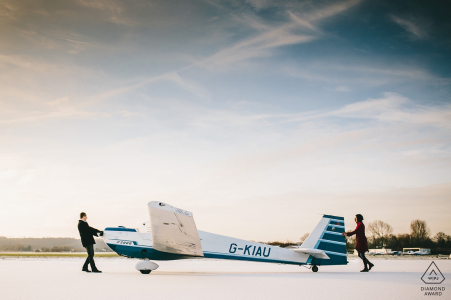 East Midlands engagement session at the airport with this couple pushing an airplane