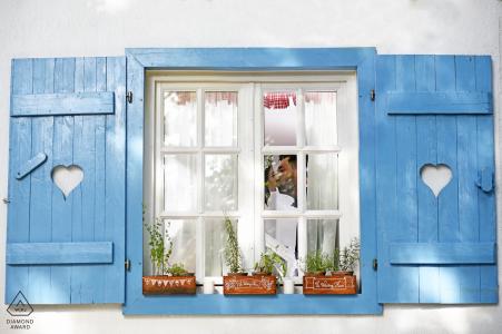 Ventana en el pueblo con jardineras y persianas enmarcadas en esta pareja rumana para su retrato de compromiso