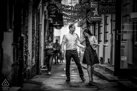 Engaged couple walks Romanian streets during their pre-wedding portrait session