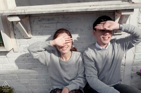Couchant le soleil de leurs yeux avec leurs mains, ce couple malaisien pose pendant leur séance de portrait précédant le mariage