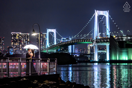 City lights, lampposts and a beautifully lit bridge enhance this formal engagement portrait