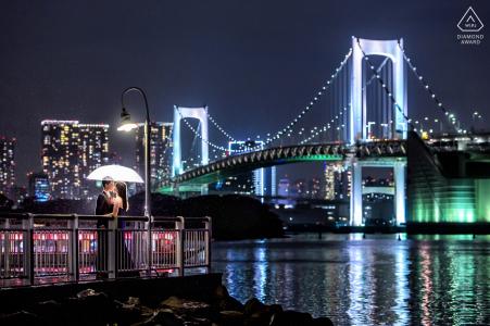 Stadslichten, lantaarnpalen en een prachtig verlichte brug versterken dit formele verlovingsportret