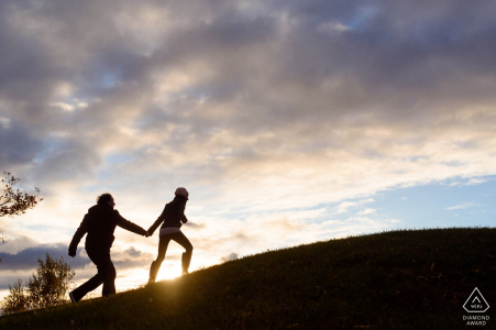 Montreal Couple running hand in hand up hill during engagement portrait session