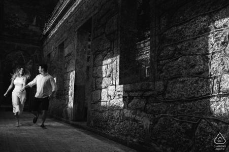 Main dans la main, ils courent sur le trottoir à côté d'un bâtiment en pierre avec la lumière du soleil lors de leur séance de portraits de fiançailles à Rio de Janeiro.