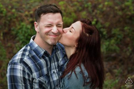Elle embrasse la joue de son fiancé alors qu'il grimace lors de leur séance de portrait avant le mariage à Atlanta en Géorgie