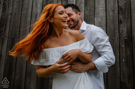 Pre-wedding engagement portraits against a wooden slatted wall for this fun-loving couple
