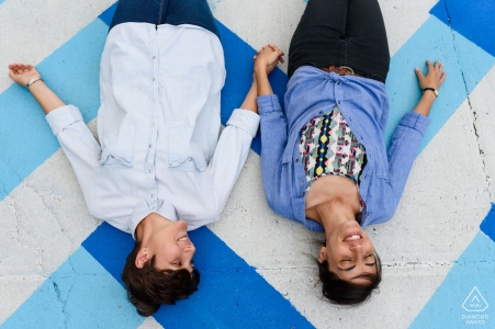 couple holding hands and lying on colourful sidewalk