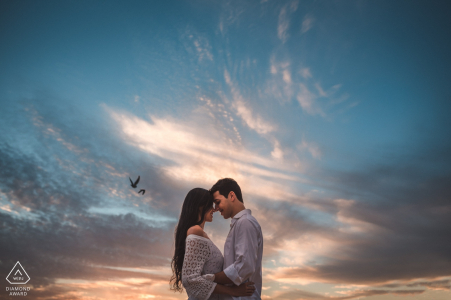 Newly engaged Rio de Janeiro couple Pose for their pre-wedding portrait against a cloud and bird filled sky