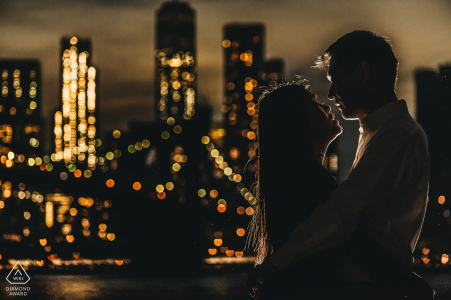 Rim lit silhouette style portrait of a couple with the city skyline in lights