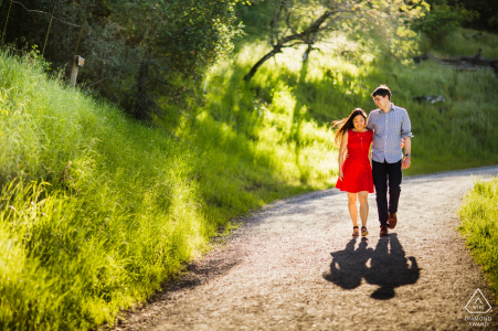 CA engagement shoot with a couple walking a dirt trail in the sun   San Francisco photographer pre-wedding pictures