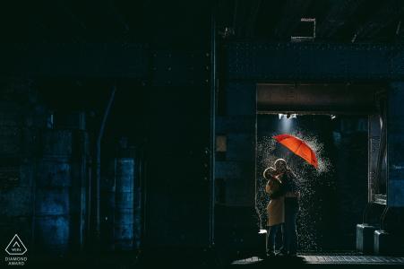 Photographie de fiançailles de portrait à Madrid sous la pluie avec parapluie rouge la nuit