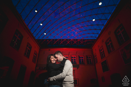 Engaged couple in love with red background during their indoor pre wedding portrait session