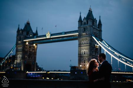 Sesión de compromiso al atardecer con una pareja en el puente de la torre