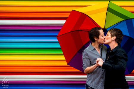 A couple kissing under a rainbow umbrella, in front of a horizontal striped rainbow mural during their engagement session