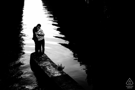 At the lake | black and white wedding engagement portrait of a couple near the water | France pre-wedding photographer session