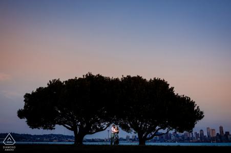 Vor der hochzeit in colorado verlobungsfotos von einem paar mit zwei großen bäumen in der abenddämmerung | Paarfotografiesitzung