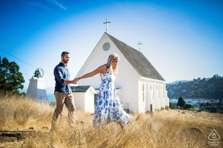 Fotos de compromiso de San Francisco de una pareja caminando junto a una pequeña iglesia antigua   Fotógrafo californiano sesión de retratos de bodas