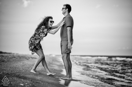 Couple laughing on the beach for engagement portraits | Fun and giggles on the beach