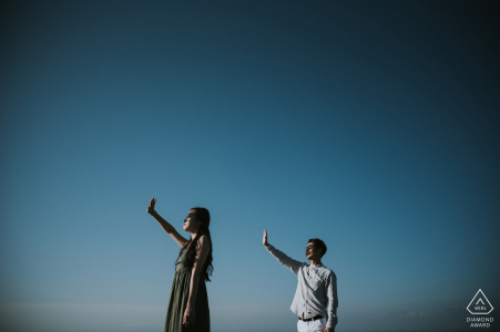 Bali pre-wedding engagement pictures of a couple blocking the sun from their eyes | couple photography session