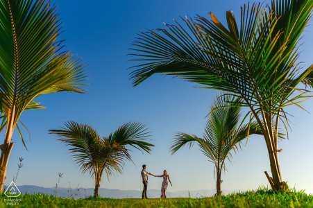 A couple is dancing under the palms during their pre wedding engagement portrait session