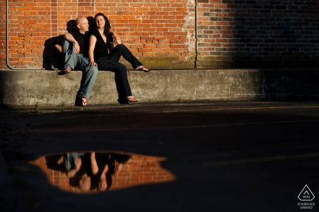 Rhode Island pre-wedding engagement pictures of a couple reflected in a puddle in the warm sun  | Providence portrait shoot