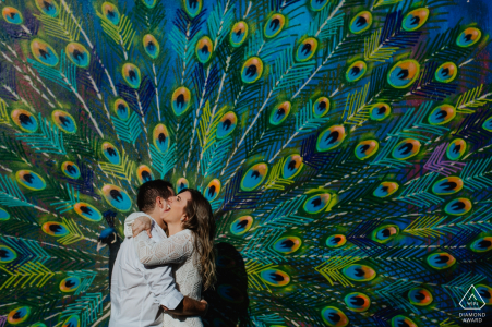 Brazil pre-wedding engagement pictures of a couple hugging before a huge peacock mural painting  | Sao Paulo couple photography session