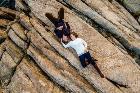 Adventerous bezet paar die op rotsen in Gloucester, doctorandus in de letteren leggen tijdens hun pre-huwelijksportretzitting.