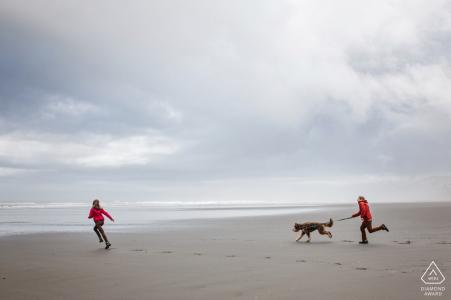 Baltimore: photos d'un couple en train de courir sur la plage avec un chien, par un photographe de mariage haut du Maryland