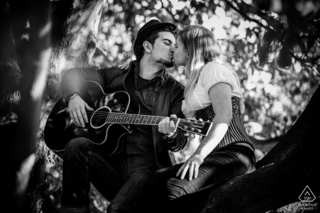 England black and white engagement photos of a couple playing the guitar in the trees while kissing  | UK photographer pre-wedding portrait session