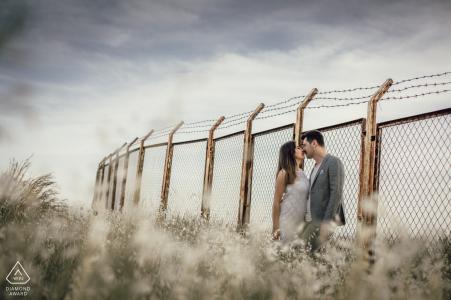 Amor en frente de la pared de alambre - Fotografía de compromiso con alambre de púas cubierto por una cerca
