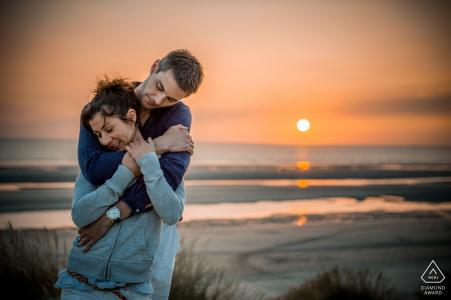 Une belle jeune couple engagé embrasse dans un câlin le dos au soleil couchant et à l'océan