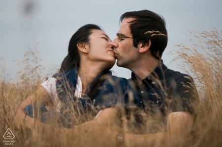 Nordsee, Alemania Retrato de compromiso de una pareja sentada en una hierba alta y tenue mientras se besa