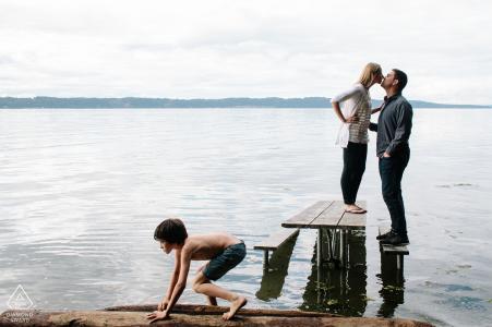 Sesión de compromiso creativo Puget Sound - Pareja besándose en una mesa de picnic en el agua