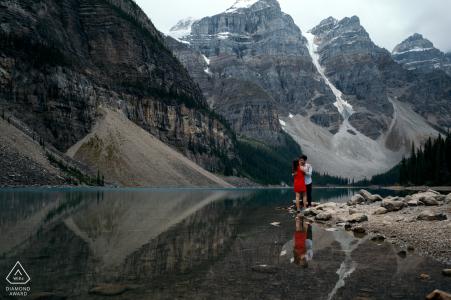 Banff-Nationalpark-Verlobungsportraitauf dem See mit einem roten Kleid und Reflexionen