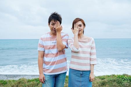 Taiwan, portrait de fiançailles symétrique Hualien à la plage | ils couvrent chacun un œil avec leurs mains