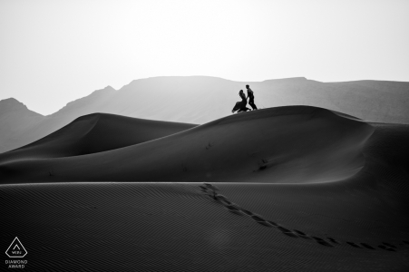 Fossil Rock, tournage d'un portrait de pré-mariage dans le désert de Dubaï - Un couple de fiancés se jetant dans le sable
